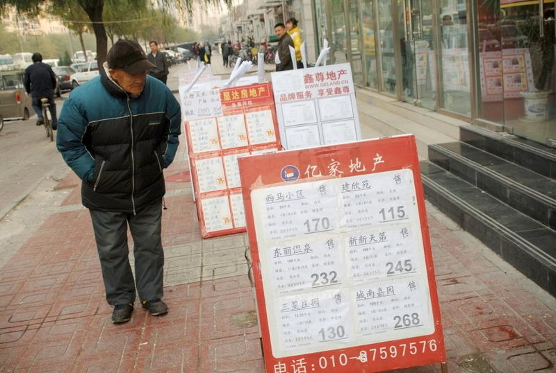 北京樓市下滑帶動周邊華北地區樓市下行。圖為北京一市民在房產中介門口看房屋價格牌。(GOU YIGE/AFP/Getty Images)