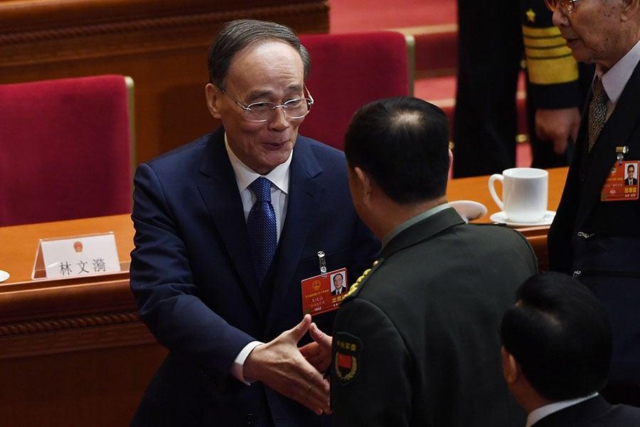 即將卸任國家軍委副主席范長龍,在人大會議上與王岐山握手,並向其行軍禮。(GREG BAKER/AFP/Getty Images)