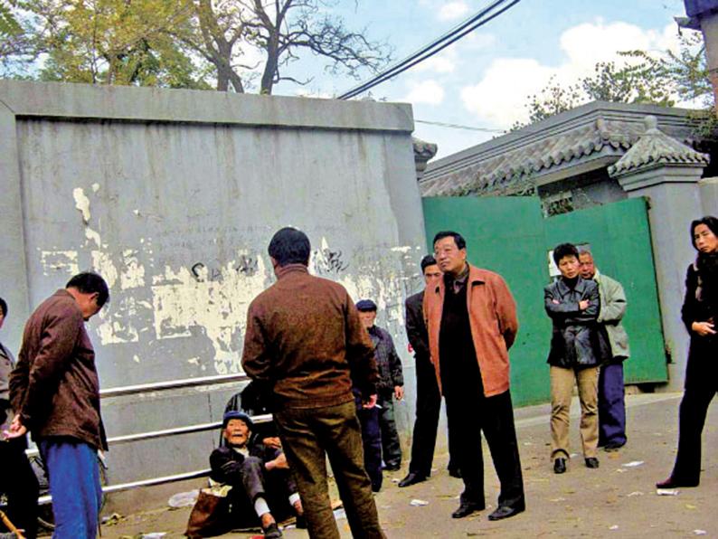 2004年11月,幾名截訪人員要拉一名上訪老人上警車。(大紀元資料圖)