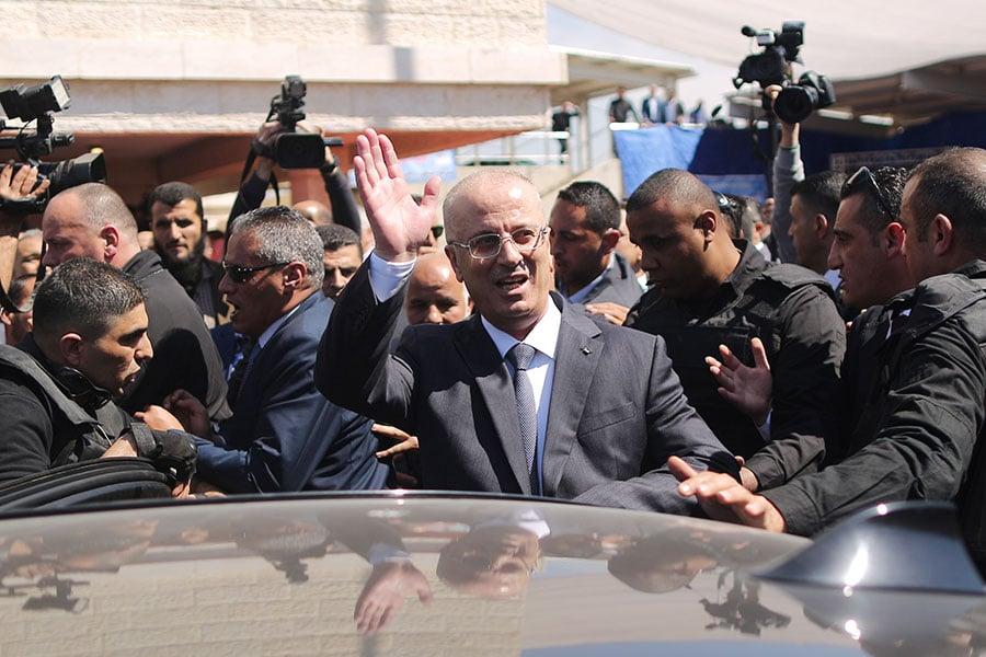 周二(3月13日),巴勒斯坦自治政府總理拉米・哈馬達拉(Rami Hamdallah)的車隊進入加沙(Gaza)時遭到炸彈襲擊,造成7人受傷。總理哈馬達拉躲過了這場暗殺。圖為哈馬達拉在加沙向群眾揮手。(MAHMUD HAMS/AFP/Getty Images)