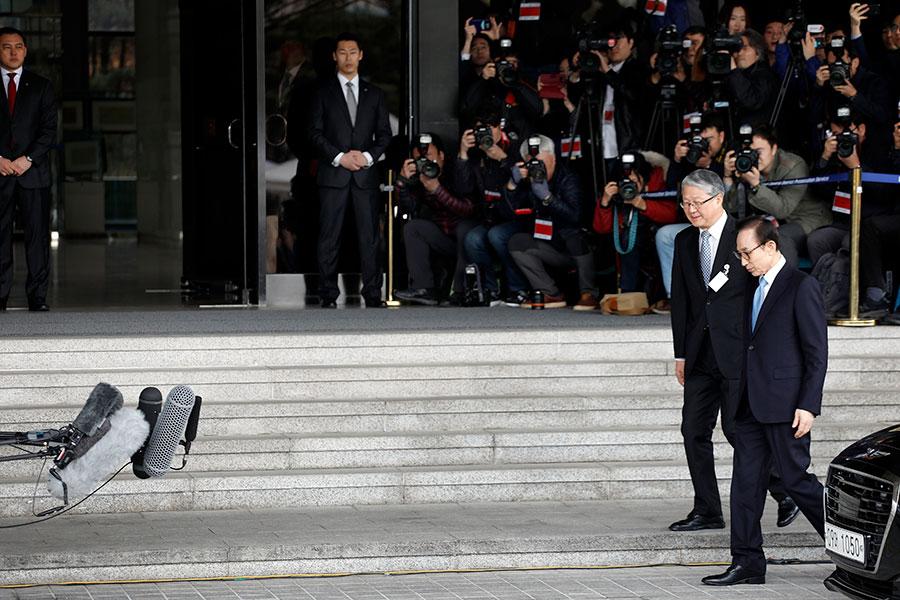 南韓前總統李明博(右一)今日(14日)以嫌疑人身份接受控方傳喚。圖為他到達首爾中央支檢的場景。(Woohae Cho/Getty Images)