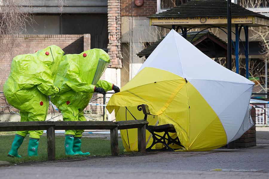 英國和俄羅斯就前俄羅斯間諜遭俄制致命毒劑毒殺案發生激烈衝突之際,另一名前俄羅斯間諜爆出自己在新西蘭曾經有過相似的經歷。圖為身穿防護服的反恐員警在斯克里帕爾父女昏倒的椅子附近進行檢查。(Matt Cardy/Getty Images)