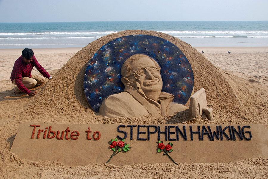 沙雕藝術家蘇達山・帕特奈克(Sudarsan Patnaik)在普里海灘上做了一個霍金的沙雕像,來紀念這位偉大的物理學家。(ASIT KUMAR/AFP/Getty Images)