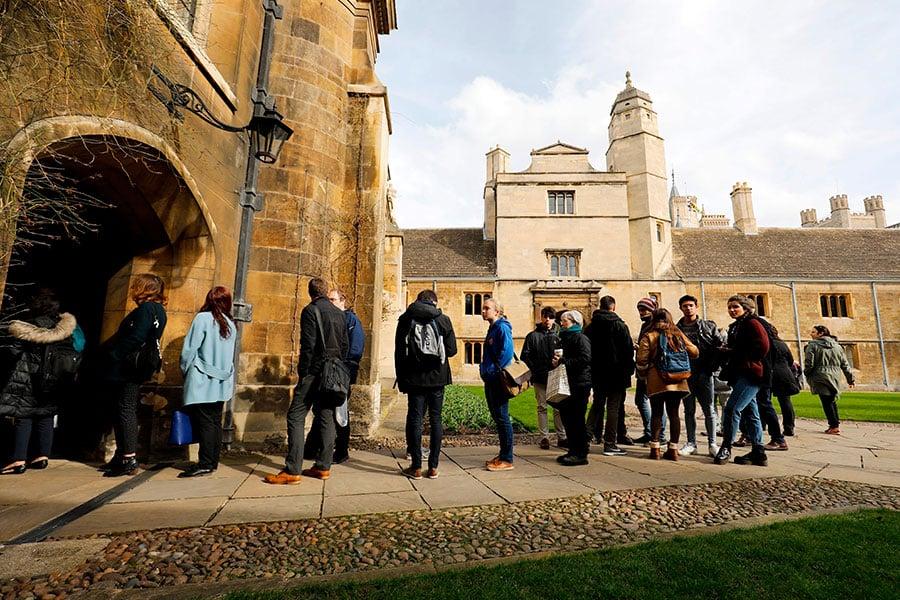 3月14日,霍金教授的死訊傳出後,學生們在劍橋大學排隊等待在悼念霍金的弔唁冊上留言。(TOLGA AKMEN/AFP/Getty Images)