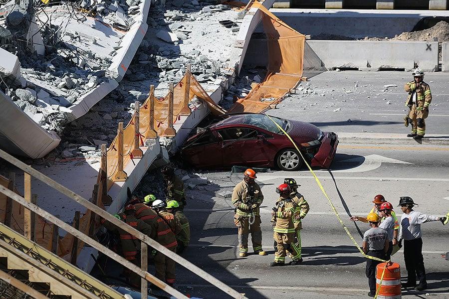 周四(3月15日),美國邁阿密佛羅里達國際大學新建的一座人行天橋坍塌,至少數人死亡,幾輛車被埋在殘骸下。(Joe Raedle/Getty Images)