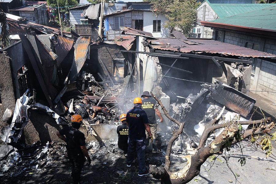 菲律賓17日一架載有5人的小型飛機墜毀在首都馬尼拉北方的住宅區,事件造成7人死亡。(AFP PHOTO/STRINGER)