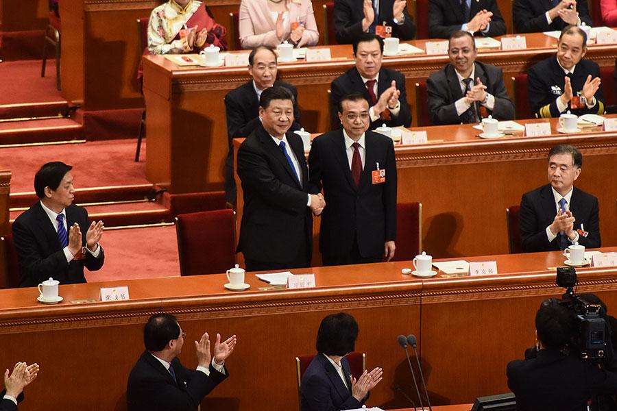 圖為3月18日,李克強獲續任國務院總理,與習近平握手。(Etienne Oliveau/Getty Images)