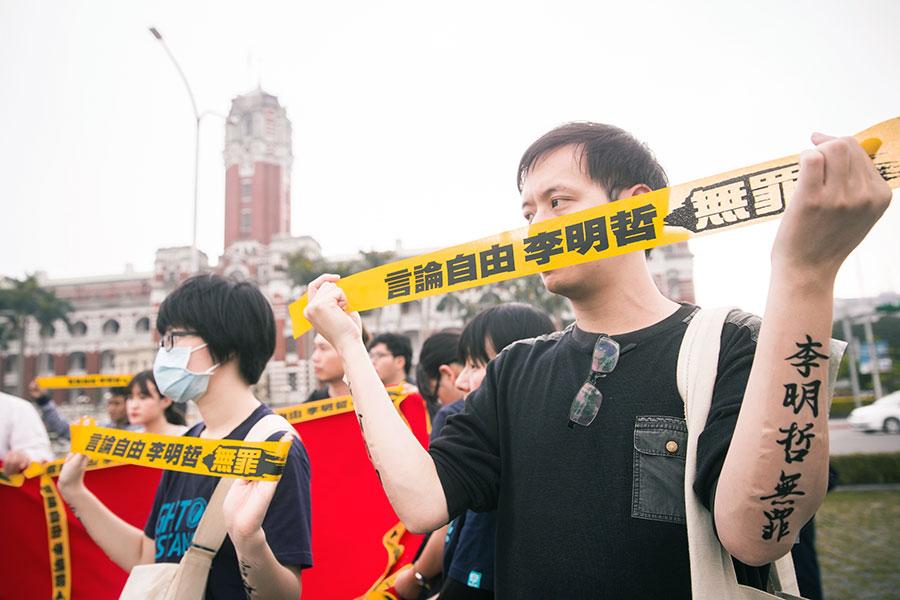 「李明哲救援大隊」19日在總統府外舉辦記者會,聲援民眾拉著黃布條、雙臂貼上「言論自由李明哲無罪」的貼紙。 (陳柏州/大紀元)