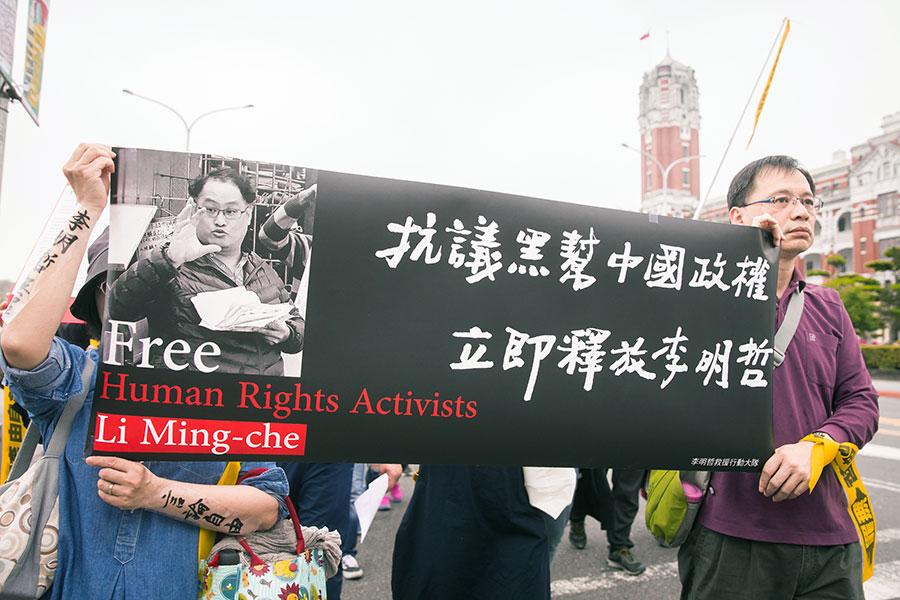 「李明哲救援大隊」19日在總統府外舉辦記者會,聲援民眾高舉「抗議中國黑幫政權 立即釋放李明哲」布條。(陳柏州/大紀元)