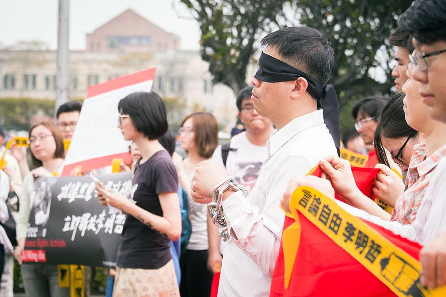 「李明哲救援大隊」19日在總統府外舉辦記者會,以行動劇表達訴求,扮演李明哲的民眾戴上眼罩及鐵鍊,象徵被中國大陸限制自由、無法與外界溝通的狀態。(陳柏州/大紀元)