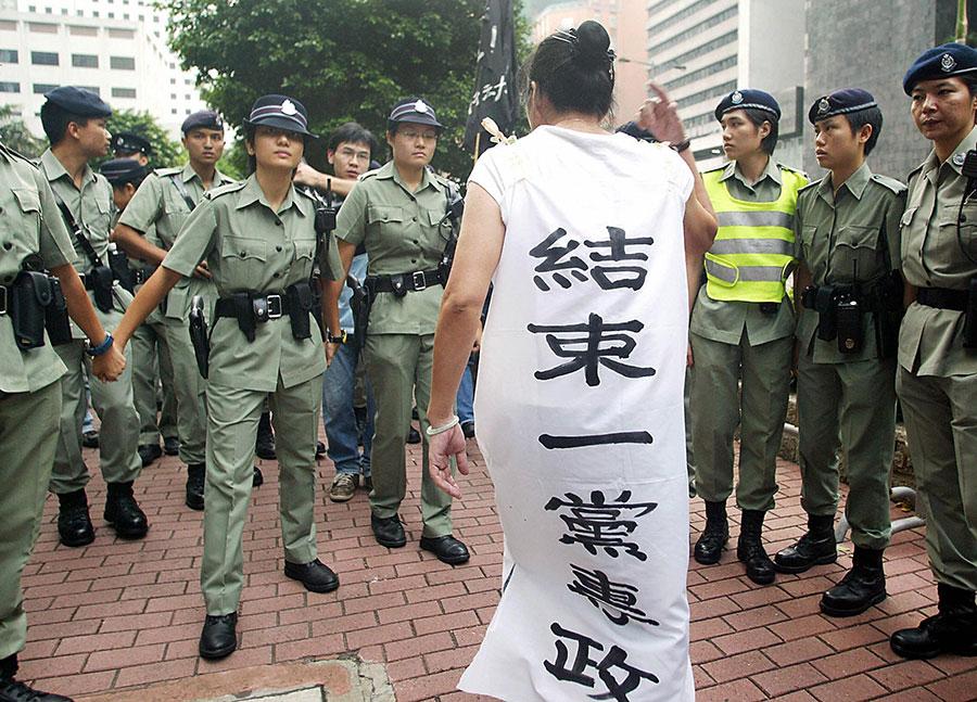 近期,人大港區常委譚耀宗聲稱,修改憲法後,再高叫「結束一黨專政」或將違法。圖為七年前香港舉行中共國慶升旗儀式後,警方布陣阻攔一身穿「結束一黨專政」橫額的抗議婦女。(SAMANTHA SIN/AFP/Getty Images)