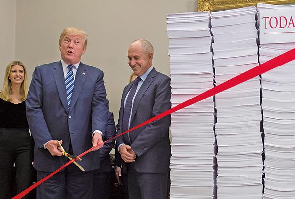 圖為特朗普去年12月14日準備剪斷繫在象徵法規文件的大堆紙上的紅帶。(SAUL LOEB/AFP/Getty Images)