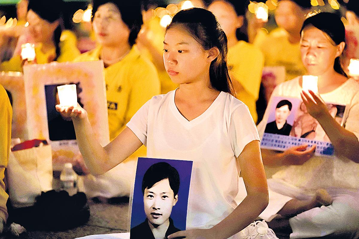 來自遼寧的十六歲女孩徐鑫洋手捧父親徐大為的遺像。徐大為因為堅持修煉法輪功被中共冤判八年監禁,出獄後十三天離世。 (大紀元)