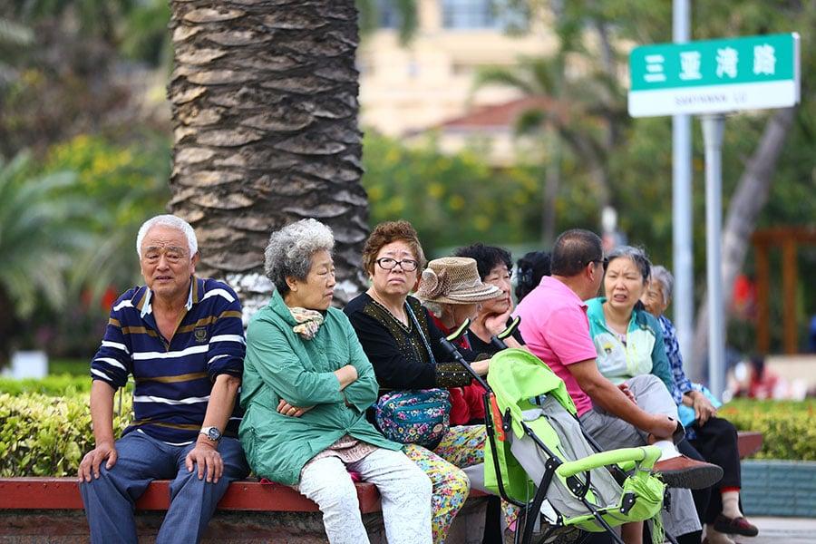 中國養老金體系面臨收不抵支的崩盤風險。圖為2017年2月15日,坐在樹下花壇邊休息的海南省三亞市老年人。(STR/AFP/Getty Images)