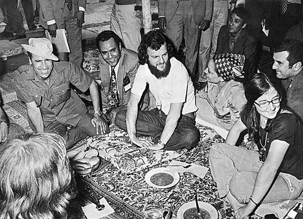 1973年卡扎菲(左)在利比亞首都的黎波里與一群英國嬉皮同樂。(AFP)