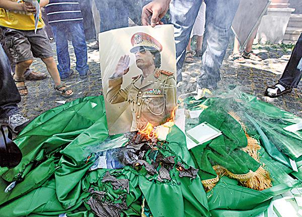 2011年8月22日示威者焚燒卡扎菲肖像和他的《綠皮書》。卡扎菲出版《綠皮書》的動機普遍被認為受《毛主席語錄》的影響。(AFP)