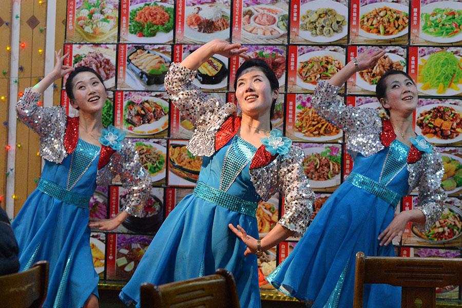 圖為2013年2月11日,丹東一家北韓餐廳的女服務員換下行頭變身歌舞演員。(MARK RALSTON/AFP/Getty Images)
