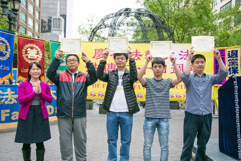 民眾於5月13日在紐約哈瑪紹廣場公園集會,慶祝第17屆法輪大法日。圖為當場三退的華人手舉退黨證書。(馬有志/大紀元)
