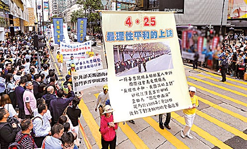 法輪功學員展示1999年4.25萬人到北京信訪辦和平上訪的歷史照片。(李逸/大紀元)