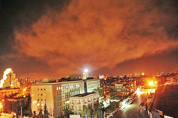 敘利亞阿拉伯通訊社發佈的一張照片顯示,英美法發動空襲時,大馬士革郊區發生爆炸。(AFP PHOTO/SANA/Handout/STR)