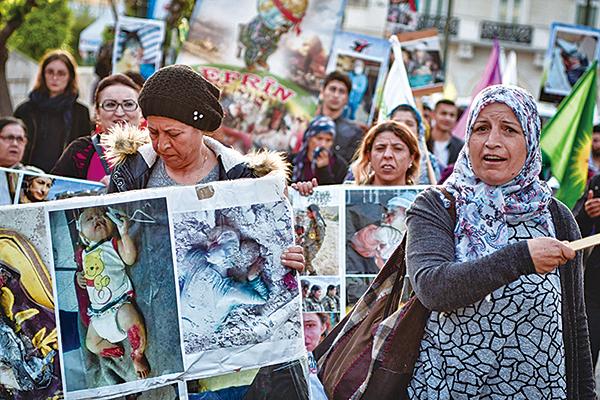 4月11日在希臘的庫爾德人在雅典的歐盟辦公大樓前請願,要求國際社會介入敘利亞阿夫林(Afrin)的屠殺事件。(LOUISA GOULIAMAKI/AFP/Getty Images)