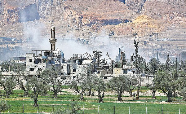 4月8日,敘利亞杜馬鎮籠罩在攻擊後的白色煙霧之中。(STRINGER/AFP/Getty Images)