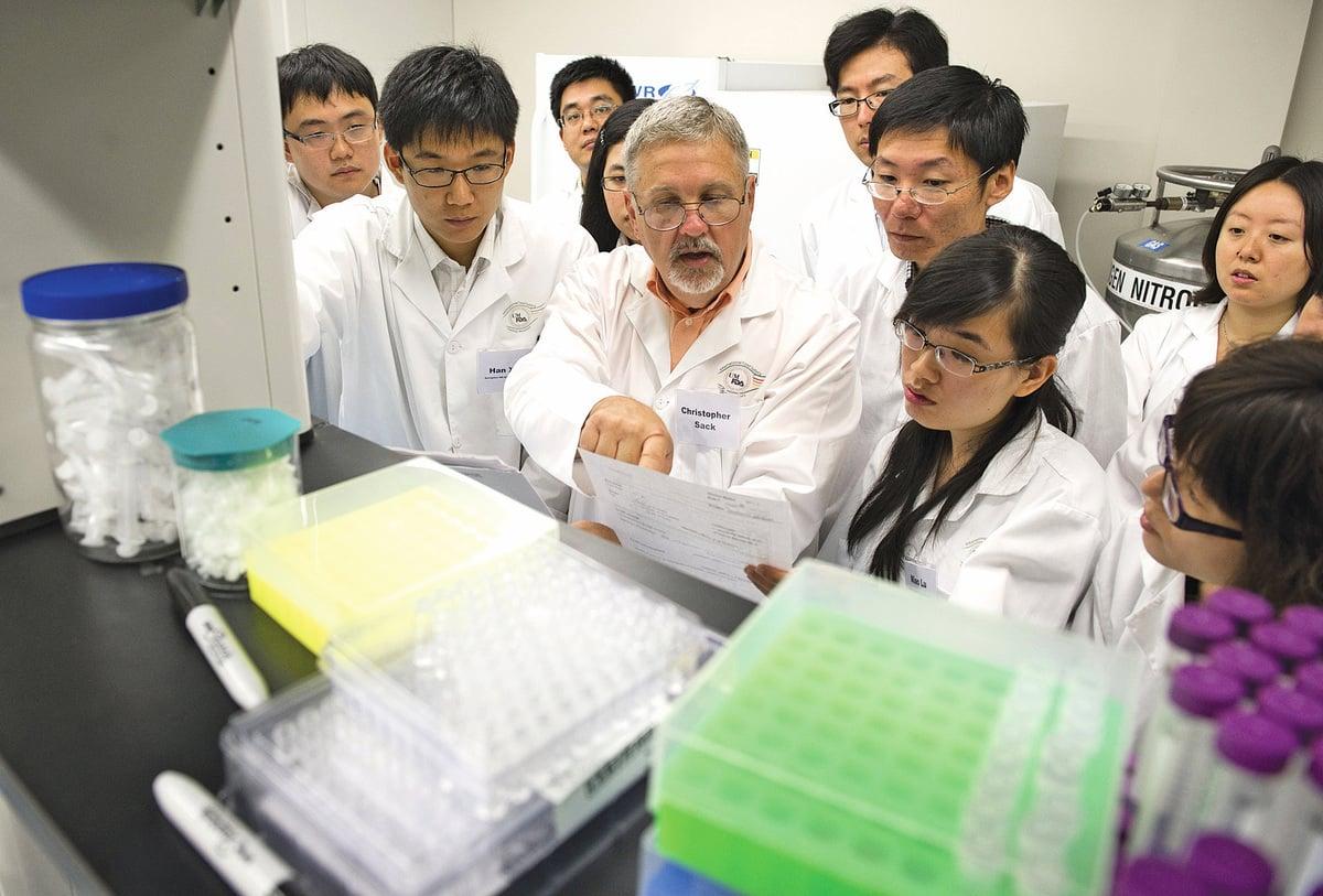 美國專家Christopher Sack (中)在馬里蘭州大學的國際食品安全培訓實驗室與來自中國和印尼的科研人員探討問題。 (AFP)