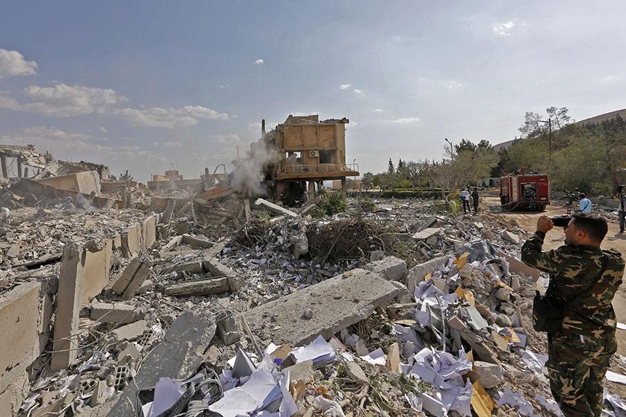 美國白宮發言人桑德斯周一表示,特朗普政府正在考慮對俄羅斯實施更多制裁,並將在近期內作出決定。一名敘利亞士兵站在被炸成廢墟Barzah科研中心。(LOUAI BESHARA/AFP/Getty Images)