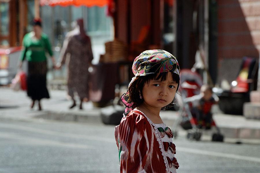 圖為2013年6月29日,一名維吾爾族小女孩在新疆烏魯木齊穆斯林區的主要集市附近。(AFP PHOTO/MARK RALSTON)