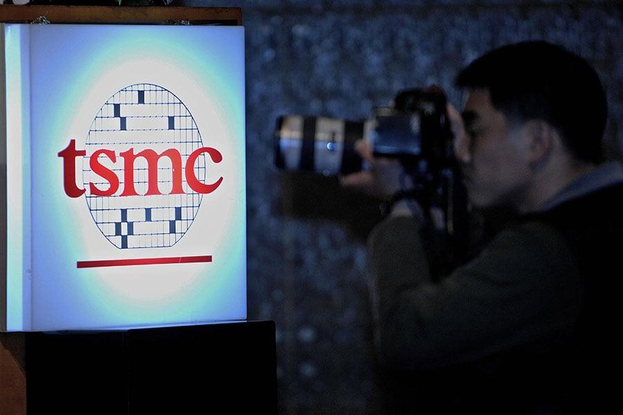 近日台積電查獲一名工程師涉嫌竊取晶圓機密,試圖提供給中共央企使用。圖為一名攝影師在台積電的標誌旁攝像。(AFP/Getty Images)