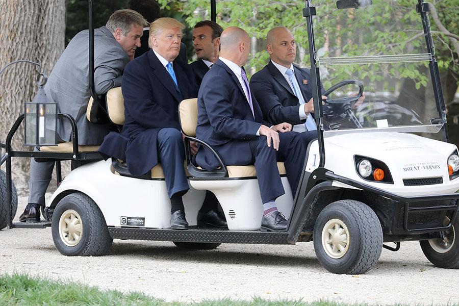 特朗普和馬克龍在維農山莊搭乘高爾夫球車。(AFP PHOTO/Ludovic MARIN)