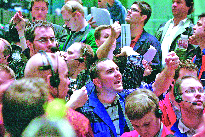 美國通脹抬頭的前景削弱了較長期國債券固定回報率的吸引力,導致國債券價格下滑,孳息率(yield)高升。圖為芝加哥交易所國債債券交易員交易間比著各種手勢。(Getty Images)