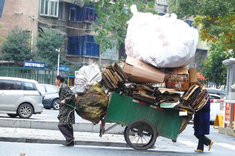 圖為中國湖南常德街頭,一個市民正在拖著超載的板車前行。(大紀元資料室)