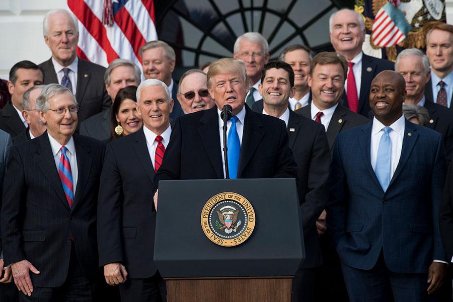 美國總統特朗普在去年12月簽署「減稅和就業法案」,目前已經使美國家庭、工人和公司受益。圖為參眾兩院通過大規模稅改案後,特朗普、副總統彭斯和共和黨國會議員在白宮慶祝。(SAUL LOEB/AFP/Getty Images)