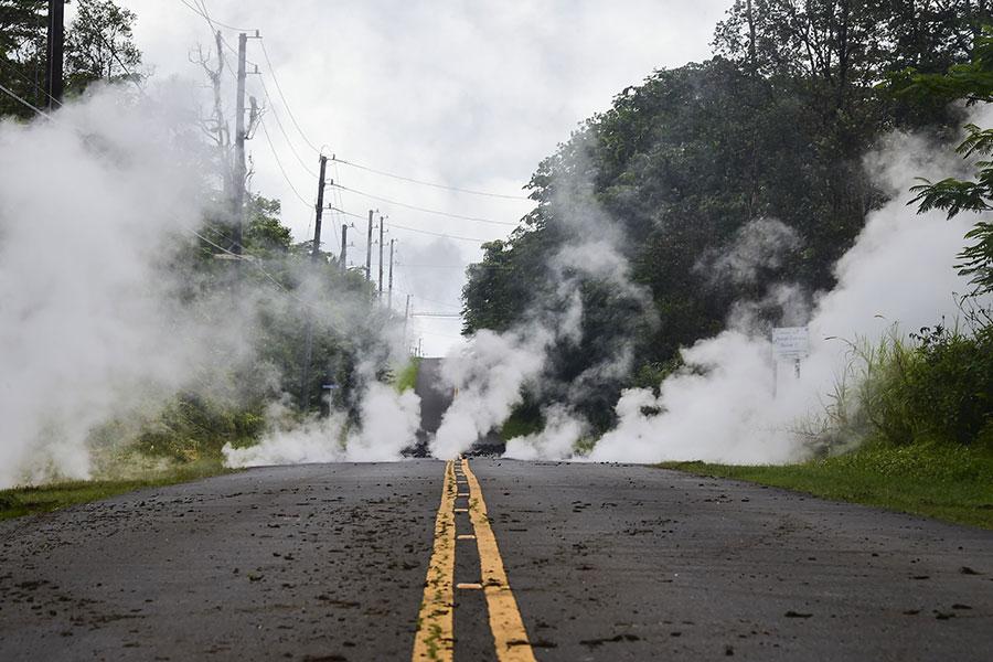 夏威夷Leilani Estates街道的一條道路上發生裂縫,冒出大量的濃煙。(AFP PHOTO/FREDERIC J. BROWN)