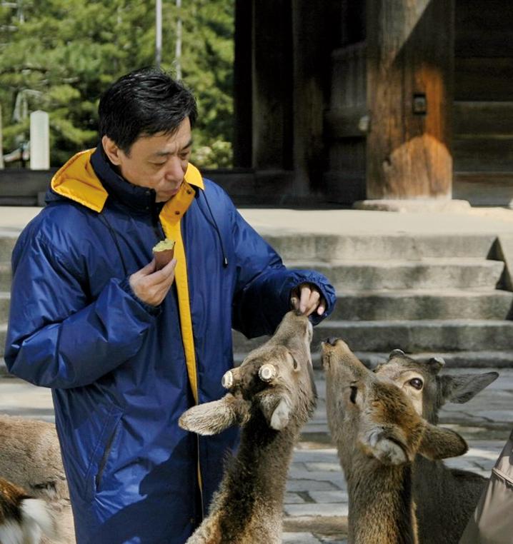 看著餵食鹿的關貴敏,臉上所散發出的善,就如他的歌聲那麼祥和。(麗莎/大紀元)