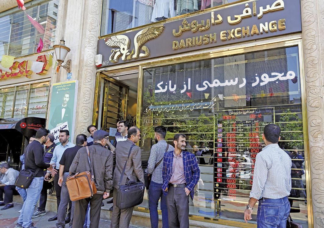 近日伊朗民眾爆發數百宗示威活動,抗議國內經濟惡化和生活艱難。圖為伊朗一家銀行外,路人關注匯率的變化。(AFP)