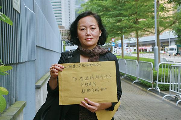 新唐人香港分台項目經理吳雪兒到特首辦公室遞信,就中聯辦脅迫港府干擾神韻租用場地一事提出抗議。(陳仲明/大紀元)