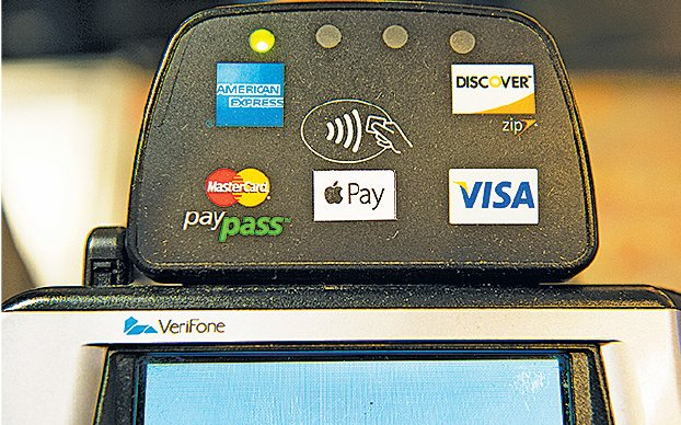 一商家收銀機上標示可接受的付款方式。(Getty Images)