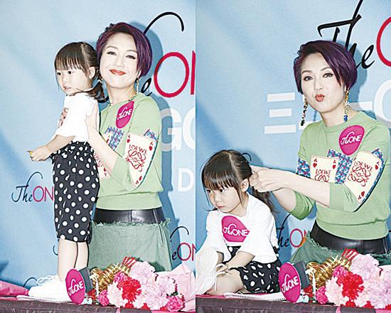 楊千嬅昨日出席簽名會活動時替小女孩紮頭髮。(互聯網)