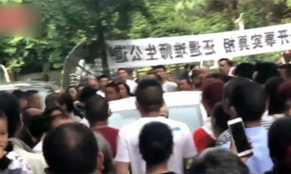 汶川地震遇難學生家屬包圍香港商業電台記者的車輛,防止身份不明者接近。(電視畫面擷圖)