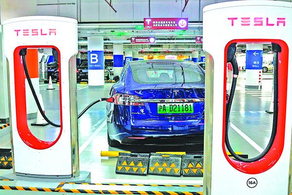 圖為上海一家購物商場內的特斯拉充電站,一輛特斯拉汽車正在充電。(AFP)