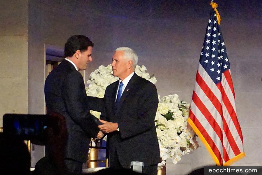美國副總統彭斯(右)與以色列大使容.德摩爾(Ron Dermer)握手。(林帆/大紀元)