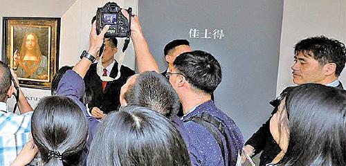 圖為去年10月13日,達文西名畫《救世主》在香港拍賣前傳媒預覽相片。李振成(最右方男子)當日在場維持秩序。(佳士得提供)