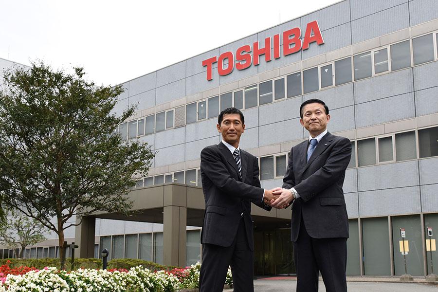 去年10月,貝恩資本的日本市場負責人Yuji Sugimoto(左)和東芝的Yasuo Naruke握手。(KAZUHIRO NOGI/AFP/Getty Images)