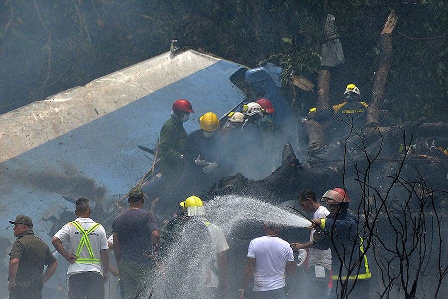 消防人員在飛機失事現場援救。(AFP PHOTO/Yamil LAGE)