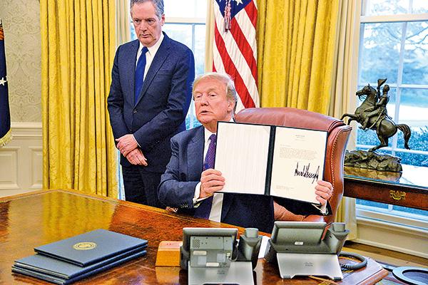 今年1月23日美國總統特朗普(右)簽署第201條規定公告,對進口洗衣機、太陽能電池及模組課徵防衛性關稅。(Mike Theiler-Pool/Getty Images)