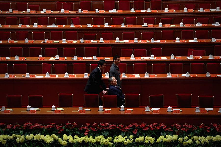 鄧小平在文革時期被批鬥,被逼著下跪、坐「噴氣式」等;他的長子鄧樸方也在被批鬥中墜樓,導致終身殘疾。圖為鄧樸方2012年11月被工作人員推離北京大會堂現場。(Feng Li/Getty Images)