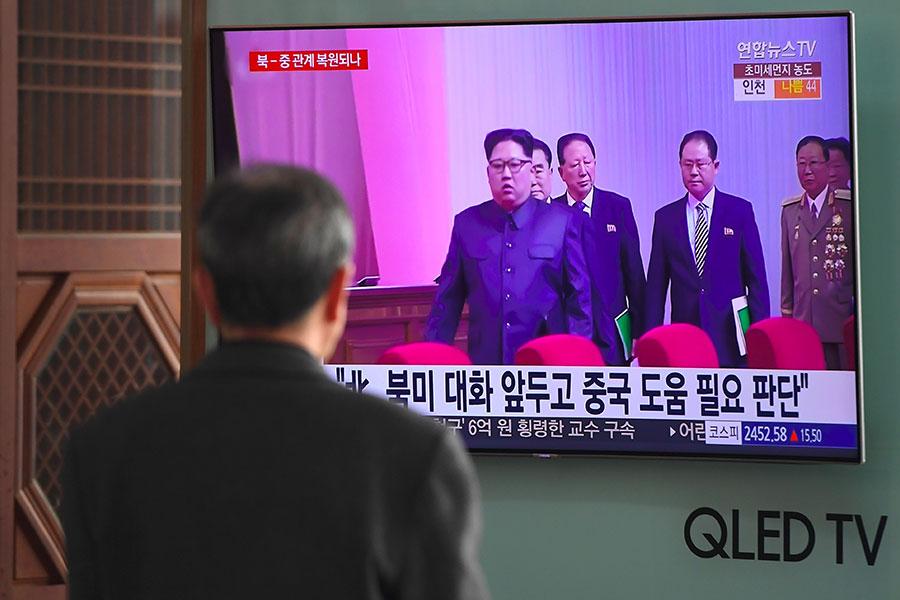 中朝兩國共產黨國家高層在美朝首腦峰會前,密集互訪,隨後北韓對南韓、美國態度轉強硬。圖為3月底電視新聞在播報金正恩訪問中國消息。(JUNG YEON-JE/AFP/Getty Images)