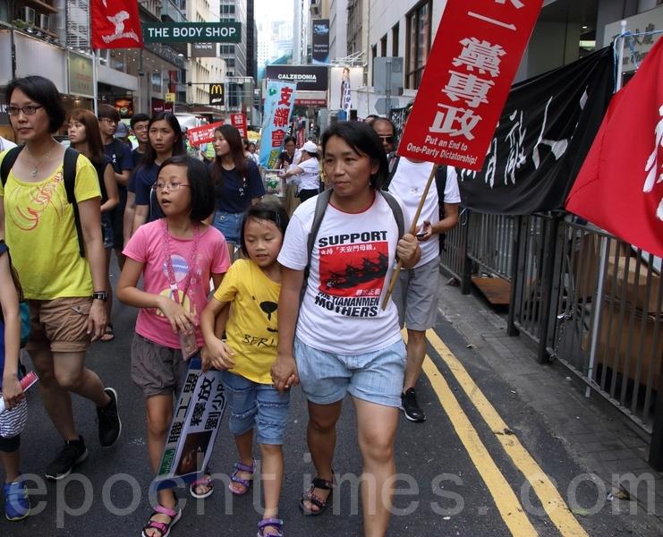 鍾女士帶同兩個女兒上街,她指中共必須承擔罪責,又強調上街是為了下一代。(蔡雯文/大紀元)